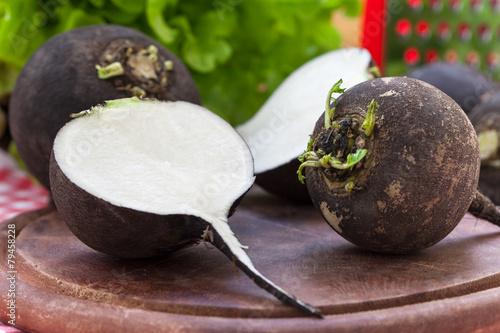 Fototapeta Black radish on wooden board
