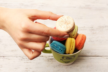 Female hand taking tasty colorful macaroons from cup