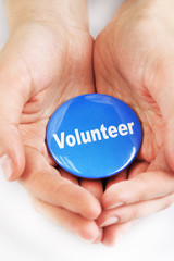 Round volunteer button in hands isolated on white