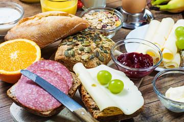 gedeckter Frühstückstisch mit Brötchen, Käse, Obst und Marmelade