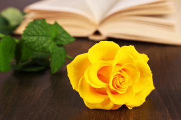 Book with yellow rose on wooden table background