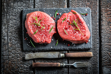 Piece of beef with fresh herbs on black rock