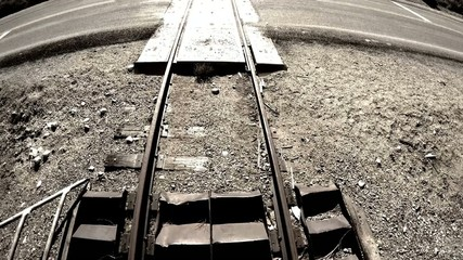 Old railroad tracks cross a highway