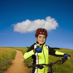 child with bicycle in the field