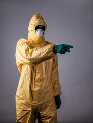 Laboratory man in chemical protective dress showing hand forward