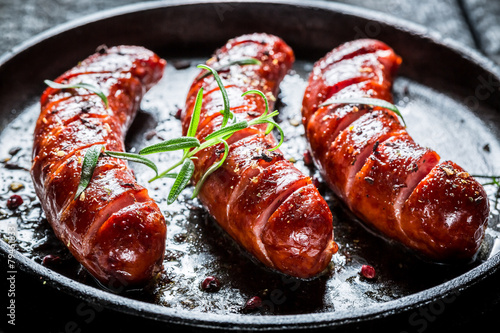 Fototapeta Grilled sausage with fresh rosemary on hot barbecue dish