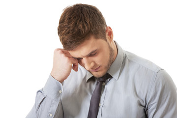 Worried businessman touching his forehead.