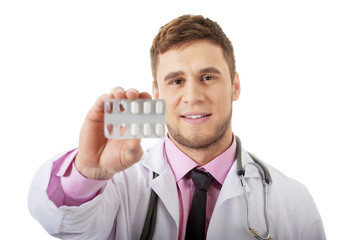 Male doctor holding pills.