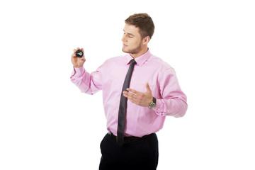 Young businessman showing billiard ball.