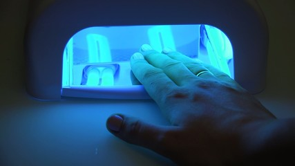 Hand in UV Lamp Nail Dryer. Woman Drying Nails. 4K Ultra HD