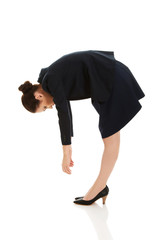 Young business woman bending down.