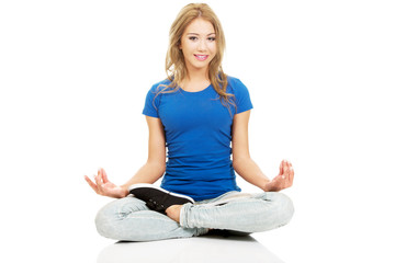 Young woman in lotus yoga pose.