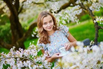 Young girl drinking tea in cherry garden