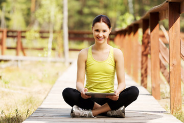Woman surfing on tablet after running