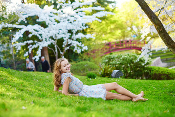 Beautiful girl in cherry blossom garden