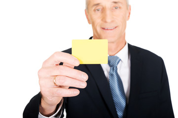 Businessman showing a yellow identity name card