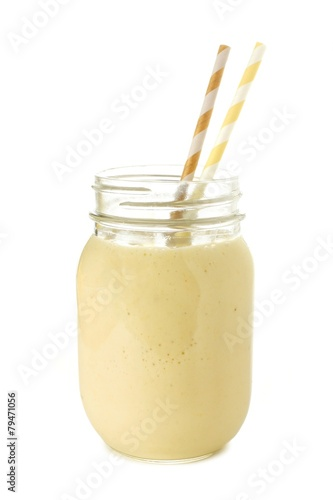 Banana smoothie in a mason jar with straws over white