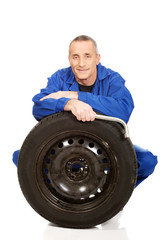 Happy mechanic with a tire and wrench