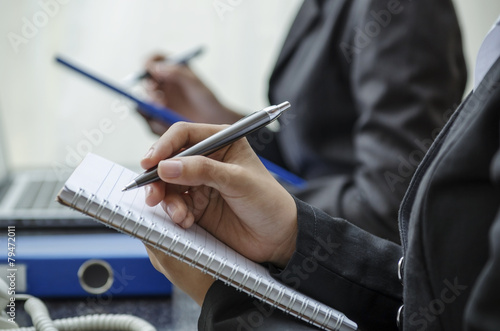 Closeup of writing hands in a row - 79472011
