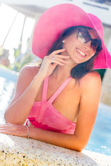 young beautiful woman relaxing in pool, summer vacations in trop