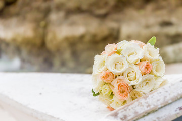 beautiful bridal bouquet of white and peach roses on natural bac