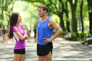 Happy runners couple talking after run in NYC park