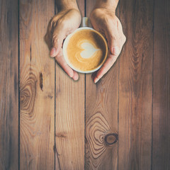 man hand holding hot cup of coffee, with heart shape