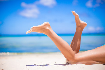 Female tanned slim legs on the white sandy tropical beach