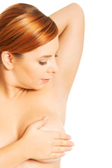 Overweight woman examining her breast