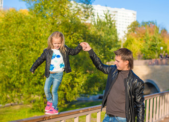 Adorable daughter and little father in autumn park outdoors