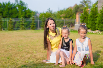 Mother and kids sitting outdoors at beautiful summer park