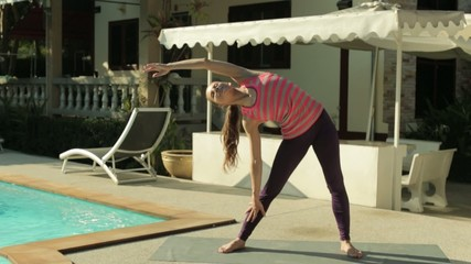 Young woman stretching at the pool