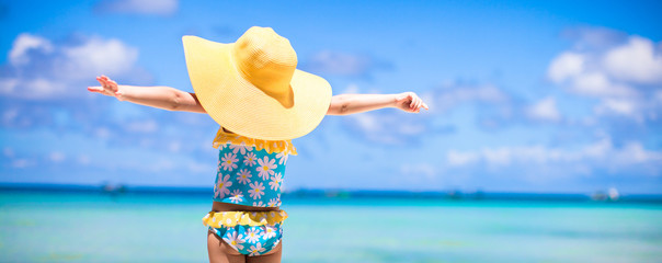 Little girl in big yellow hat on white sandy beach