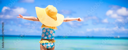 Little girl in big yellow hat on white sandy beach - 79479038
