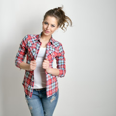 Beautiful teen girl with jeans and checkd shirt. Fashion girl.