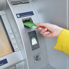 Woman withdrawing money from credit card at ATM, hand closep.