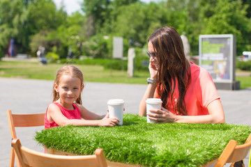 Young mother and her little girl at outdoor cafe on warm day