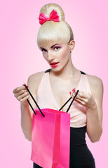 Woman holding shopping bag isolated on pink background