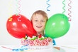 Little boy with a festive cake and balloons
