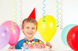 Little boy in holiday hat with a birthday cake and balloons