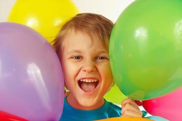 Little smiling boy between the festive balls