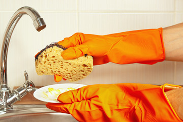Hands in rubber gloves with sponge and dirty plate over the sink