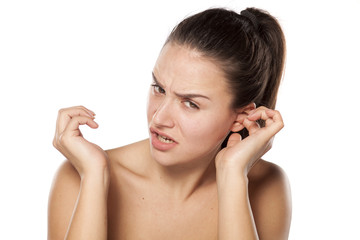 young woman has itching in the ear