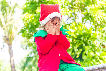 young happy child dressed as santa helper elf, xmas costume, gre