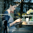 Young woman drinking coffee and use her smartphone sitting indoo