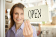 Store Owner Turning Open Sign In Shop Doorway - 79485661