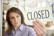 Leinwanddruck Bild - Store Owner Turning Closed Sign In Shop Doorway