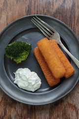 Fried fish fingers with broccoli and tartar sauce.