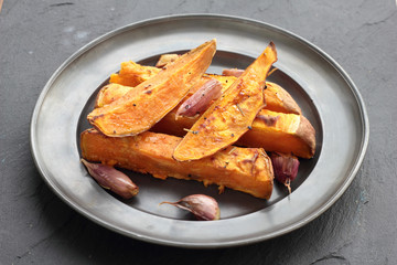 Sweet potato roasted chips on a tin plate.