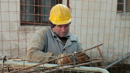 Old worker with helmet on head tied rebar with tongs and wire